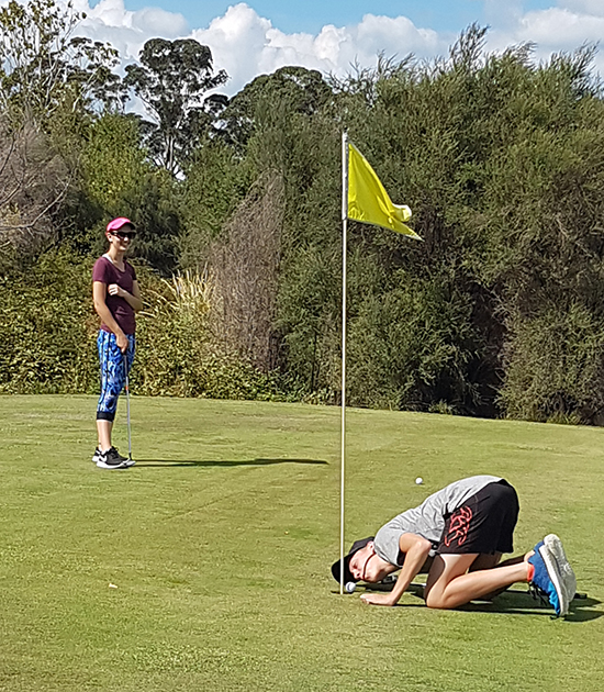 Javier blowing the ball in during golf
